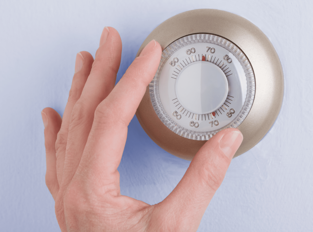 hand adjusting the thermostat