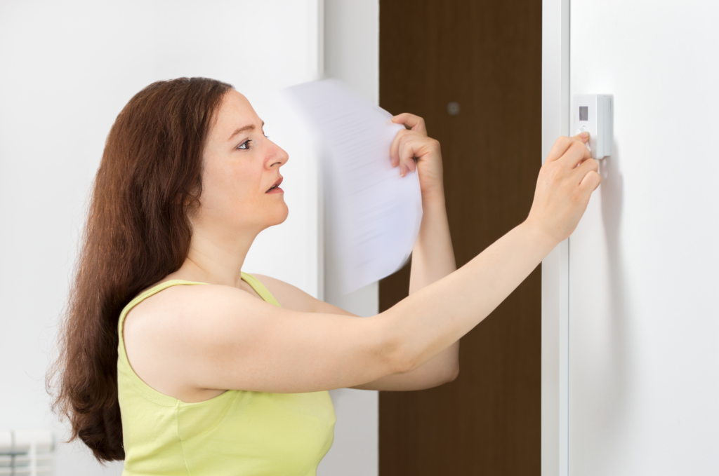 woman turning thermostat to cold air